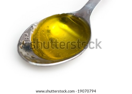 Spoon with extra virgine olive oil - stock photo