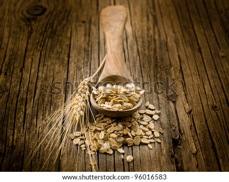 spoon with oat on wood background - stock photo