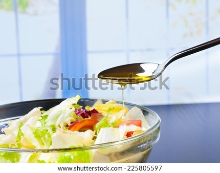spoon with olive oil on italian fresh salad on window background nutrition concept - stock photo