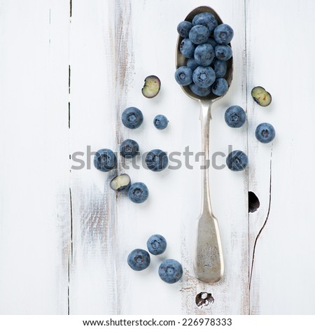 Spoon with ripe blueberries, white wooden surface, above view - stock photo
