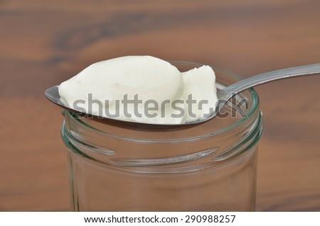 Spoon with yoghurt - stock photo