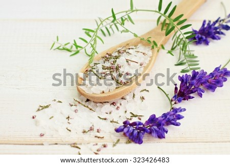 spoonful of aromatic herbal salt mixture with herbs flowers, organic product, white wooden table - stock photo