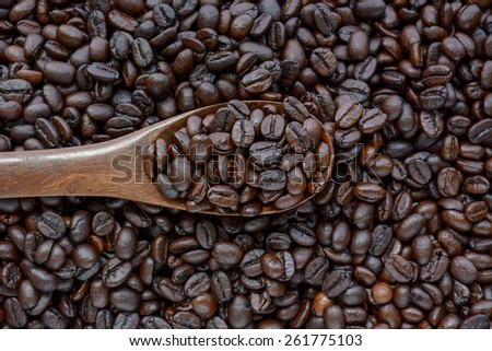 Spoonful of coffee beans on coffee bean heap - stock photo