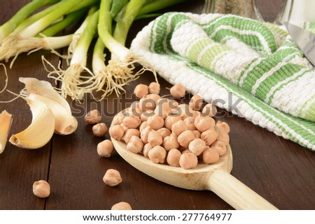 Spoonful of dried garbanzo beans with garlic cloves and green onions - stock photo