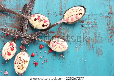 Spoons with tasty chocolate for party on old blue wooden table - stock photo