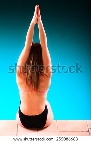 Sport active lifestyle. Sporty woman female swimmer muscular fit body preparing to jump into swimming pool back view - stock photo