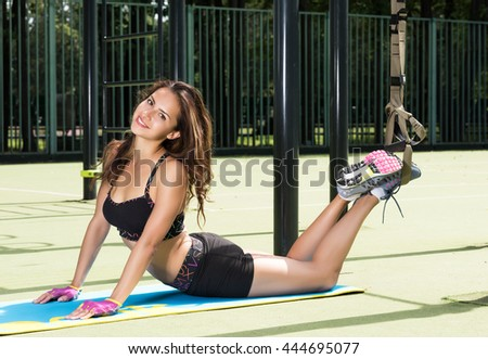 Sport activities outdoors. Exercises with straps. Beautiful young woman in sportswear lying on the rug. Street in the background area - stock photo