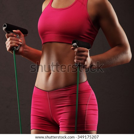 Sport, activity. Cute woman with skipping rope. Muscular girl black background. - stock photo