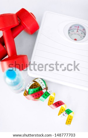 sport and diet concept - scales, dumbbells, bottle of water and measuring tape - stock photo