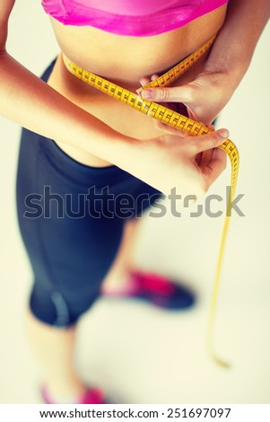 sport and diet concept - trained belly with measuring tape - stock photo
