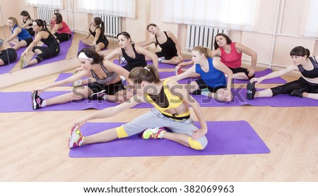 Sport and Fitness Concept. Group of Seven Female Athletes Performing Stretching Exercises On Sport Mats indoors.Horizontal Image - stock photo