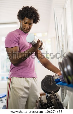 Sport and fun, young african american male athlete taking weights from shelf in fitness club - stock photo