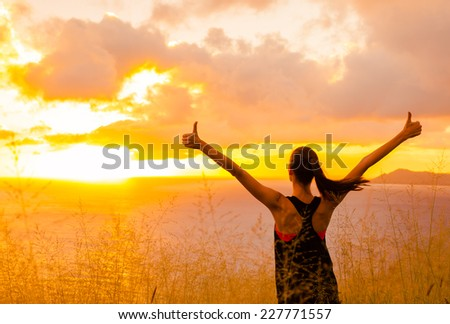 Sport and life achievements and success concept.. Sporty girl raising arms towards beautiful glowing sunshine.  - stock photo