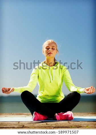 sport and lifestyle concept - woman doing yoga outdoors - stock photo