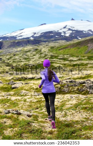 Sport athlete woman - exercising trail runner running. Active female fitness model training and jogging outdoors in beautiful mountain nature landscape by Snaefellsjokull, Snaefellsnes, Iceland. - stock photo