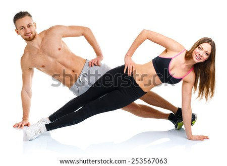 Sport attractive couple - man and woman doing fitness exercises on the white background - stock photo