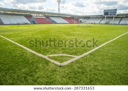 Sport background of empty football field with fresh green grass against blue sky with clouds and empty stadium with scoreboard Space for people or objects  - stock photo