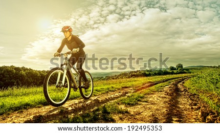 Sport bike woman on a meadow with a beautiful landscape - stock photo