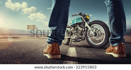 Sport. Biker standing near the motorcycle on an empty road at sunny day. Close view on legs - stock photo