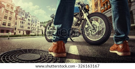 Sport. Biker standing near the motorcycle on the street at sunny day. Close view on legs - stock photo
