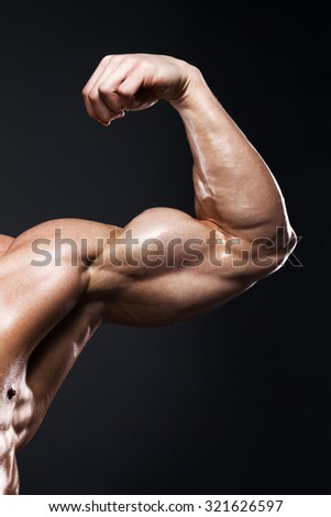 sport, bodybuilding, strength and people concept - close up of young man flexing and showing biceps over dark background with clipping path - stock photo