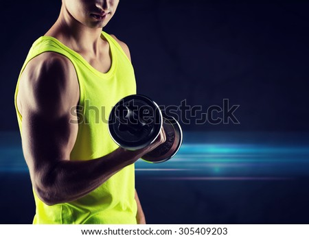 sport, bodybuilding, training and people concept - close up of young man with dumbbell flexing biceps over dark background - stock photo