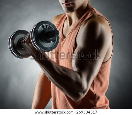 sport, bodybuilding, training and people concept - young man with dumbbell flexing muscles over gray background - stock photo
