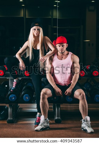 sport, bodybuilding, weightlifting, lifestyle and people concept - Young beautiful couple in stylish clothes sitting a gym near the dumbbells - stock photo
