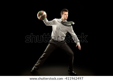 sport businessman plays basketball on black background - stock photo