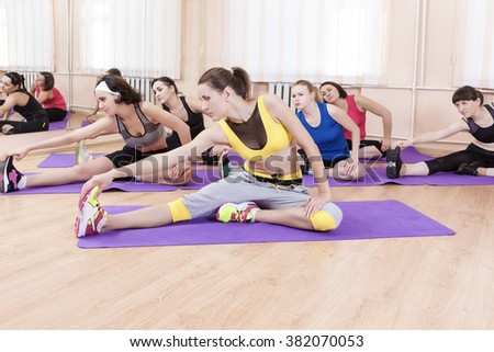 Sport Concept and Ideas. Female Caucasian Athletes Doing Fitness Stretching of Legs Muscles Indoors. Horizontal Shot - stock photo
