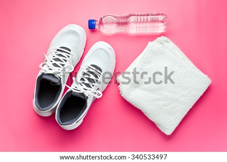 sport concept. bottle, shoes and towel on pink background - stock photo