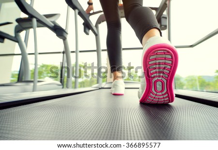 Sport concept. Close up of running female feet in sneakers in gym. - stock photo