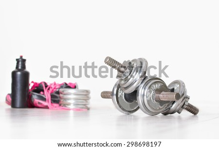 Sport concept. Close up of two steel dumbbells and pink sneakers and bottle of water in background - stock photo