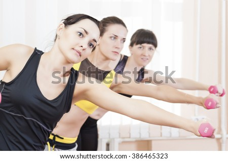 Sport Concepts. Three Caucasian Fit Women Performing Exercises With Barbells Indoors. Horizontal Shot - stock photo