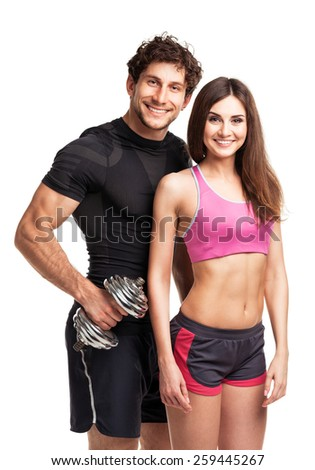 Sport couple - man and woman with dumbbells on the white background - stock photo