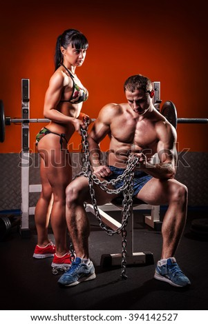 Sport couple showing muscles and workout in the gym. - stock photo