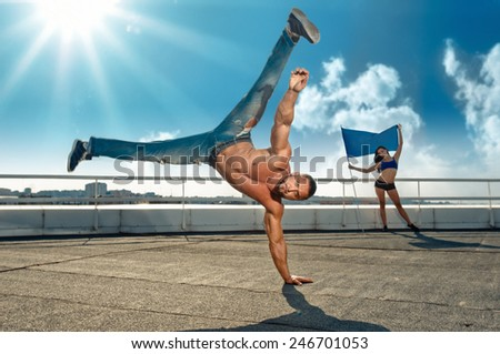 sport, dancing, man doing handstand, girl with flag on background, focus on man face - stock photo