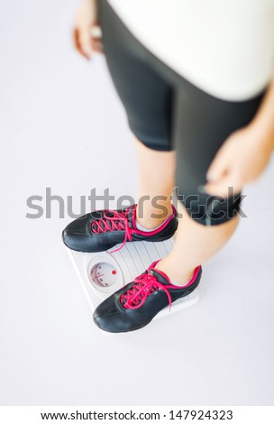 sport, diet and weight loss concept - woman legs standing on scales - stock photo