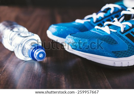 Sport equipment. Sneakers and water on wooden background - stock photo
