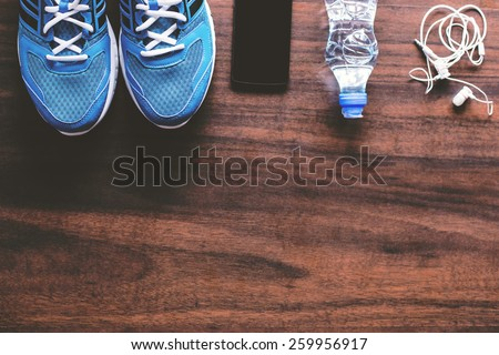 Sport equipment. Sneakers, water, earphones and phone on wooden background. Focus is only on the sneakers. - stock photo