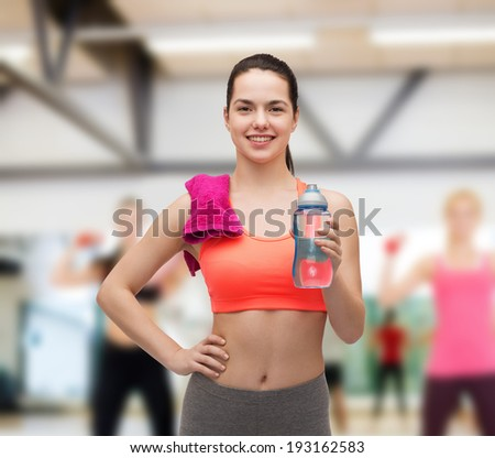 sport, exercise and healthcare - sporty woman with pink towel and water bottle - stock photo