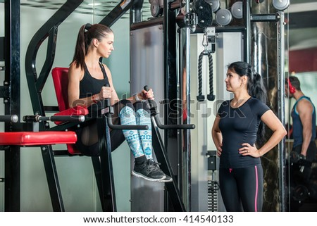 Sport exercises of the waist. Woman manager shows the client the waist how to exercise in the gym. - stock photo