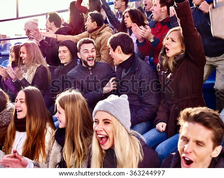 Sport fans clapping and singing on tribunes. - stock photo
