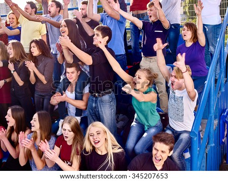 Sport fans clapping hand up  and singing on tribunes. Group people. - stock photo