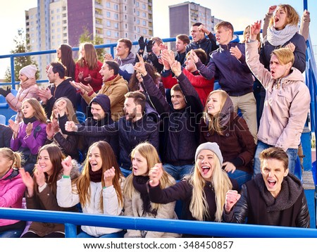Sport fans hands up clapping and singing on tribunes. Group people. - stock photo