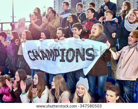 Sport fans holding very big champions banner  and singing on tribunes. Group people. - stock photo