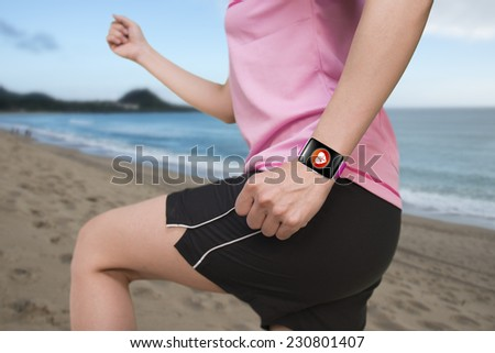 sport female wearing bright pink watchband bent touchscreen smartwatch with red health icon on natural sea beach background - stock photo