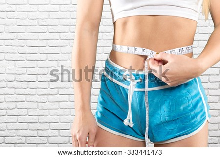 sport, fitness and diet concept - close up of trained belly with measuring tape - stock photo
