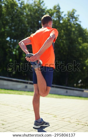 Sport, fitness and healthy lifestyle concept - man doing warm-up stretching exercise before run outdoors. Shallow depth of field, selective focus - stock photo