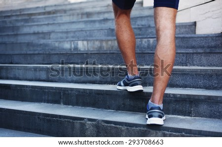 Sport, fitness and healthy lifestyle concept - man running in the city, feet of male runner on steps of stairs closeup over urban background - stock photo